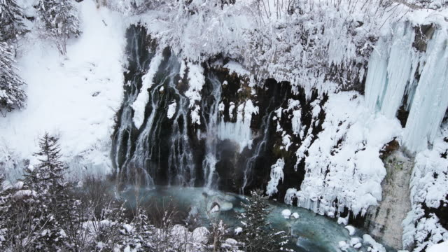 remote waterfall in snowy hokkaido landscape, high angle - kamikawa subprefecture stock videos and b-roll footage
