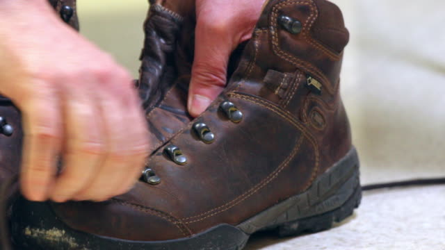 removing laces hiking shoes. - only mature men stock videos & royalty-free footage