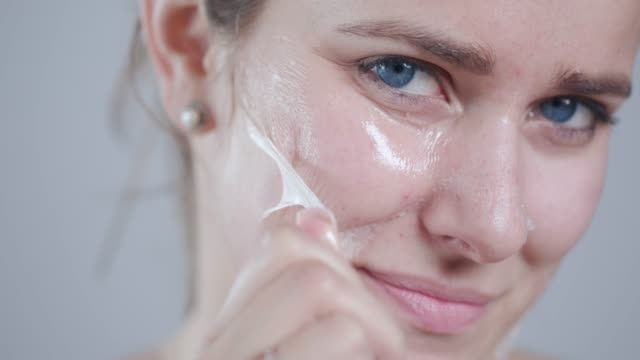 removing peel off mask from face - scrubbing stock videos & royalty-free footage