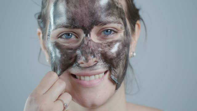 removing peel off mask from face - facial mask beauty product stock videos and b-roll footage