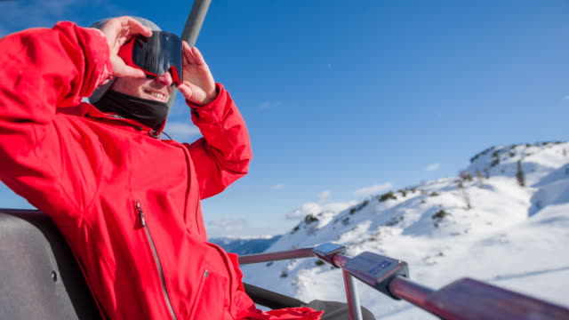 removing ski goggles while riding on chairlift to soak in the winter sun - ski goggles stock videos & royalty-free footage