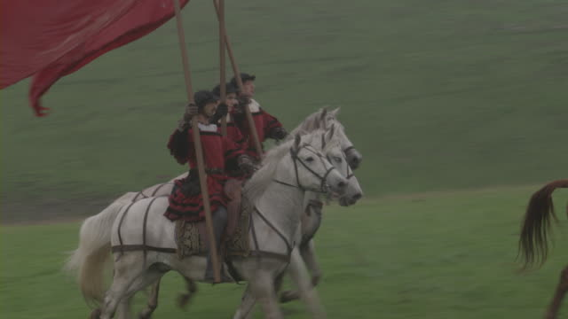 Renaissance royal guards holding flags and spears while riding on horses across a meadow.