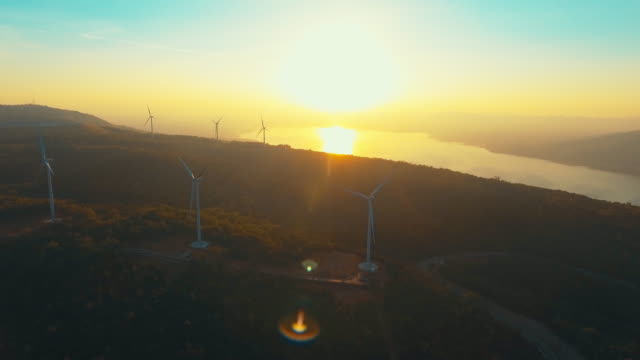 vídeos de stock e filmes b-roll de renewable energy plants:turbines at sunset - gerador