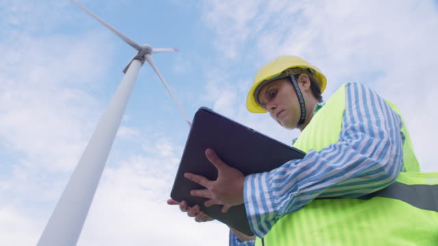 renewable energy systems. electricity maintenance engineer working on the field at a wind turbine power station with a clear blue sky behind her. - construction industry stock videos & royalty-free footage
