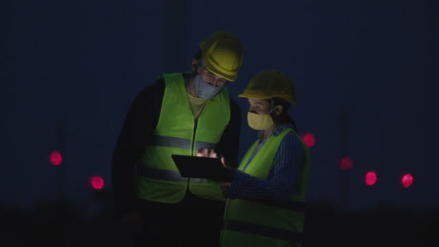 renewable energy systems. electricity maintenance engineers coworking on the field near wind turbine power station. two colleagues engineers wearing protective face masks during the covid-19 pandemic. working late at night. teamwork. - environment stock videos & royalty-free footage