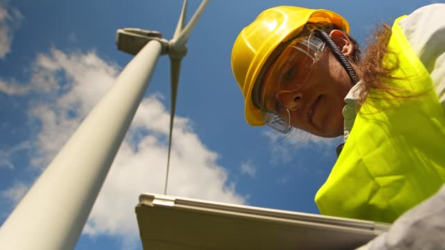 renewable energy systems engineering in a wind turbines farm. electricity  maintenance engineers working on the field near wind turbine power station with a clear blue sky behind them. - engineering stock videos & royalty-free footage