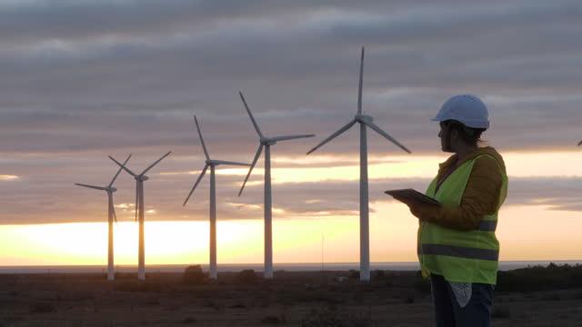 vídeos y material grabado en eventos de stock de sistemas de energías renovables. cámara lenta del ingeniero de mantenimiento de electricidad trabajando en el campo en una central de turbina eólica al amanecer. poder femenino. - explorar nuevo territorio