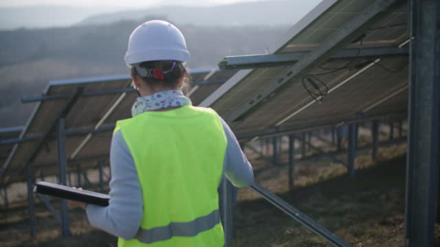 renewable energy systems. solar panels. maintenance engineer working on the field in a solar power station. - cable stock videos & royalty-free footage