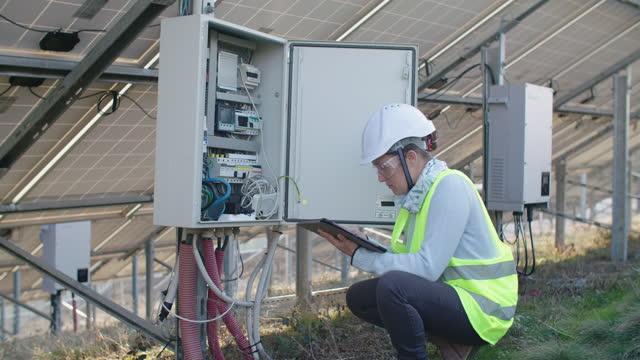 vídeos de stock, filmes e b-roll de sistemas de energia renovável. painéis solares. engenheiro de manutenção trabalhando no campo em uma usina solar. - power supply
