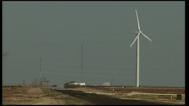 wind farm in rural Texas Close up shot wind turbine with three white aerodynamic blades / Rural windmill spinning / Wind turbine spinning / Various...