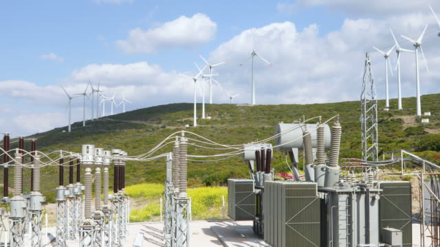 vídeos de stock e filmes b-roll de renewable green energy - power substation and wind turbines - gerador