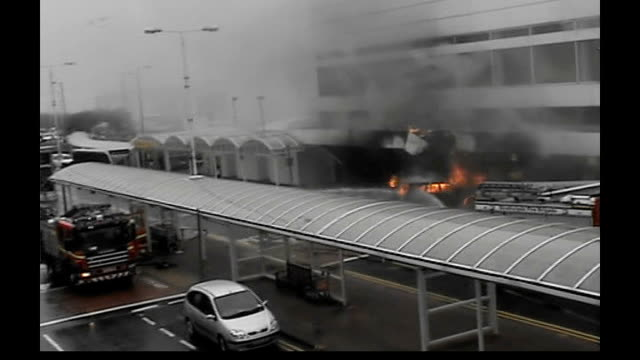renfrewshire: glasgow airport: ext amateur video footage of firefighters hosing down burning jeep car that has been driven into front of glasgow... - the glasgow airport attack stock videos & royalty-free footage