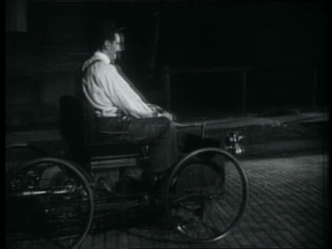 B/W rennactment 1890s PAN man (actor as Henry Ford) drives quadricycle on cobblestone street / night