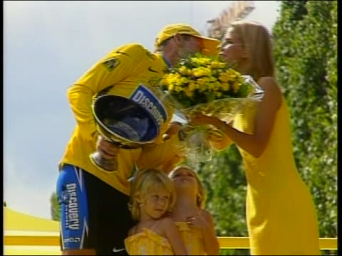 stockvideo's en b-roll-footage met renown cyclist lance armstrong, won the tour de france. he shakes a person's hand, and receives flowers from sheryl crow, and then kisses her on the... - sport