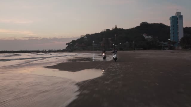 vidéos et rushes de rental scooters riding on hua hin beach, prachuap khiri khan province, thailand, southeast asia, asia - scooter