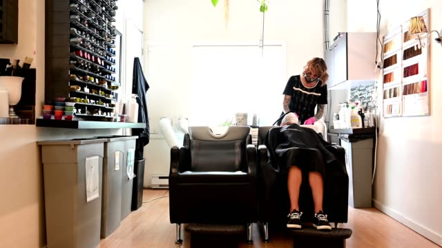 reopening a beauty salon with coronavirus safety measures - washing hair stock videos & royalty-free footage