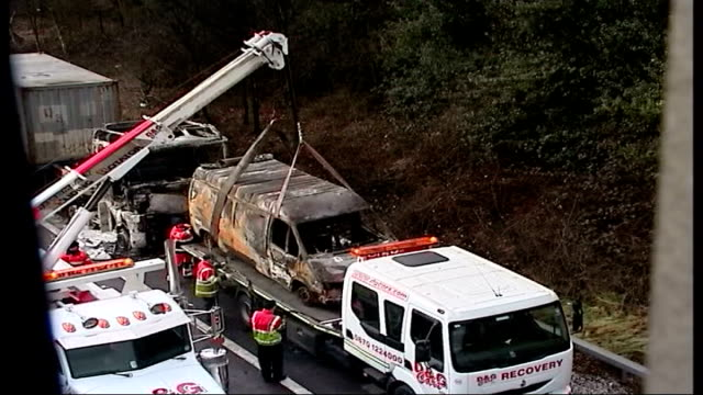 vídeos y material grabado en eventos de stock de reopens after fire; england: essex: ext burnt out van being hoisted onto recovery lorry by crane on side of motorway wreckage of burnt out cabin of... - bare tree