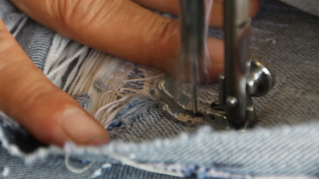 repair denim with sewing machines. - sewing stock videos and b-roll footage