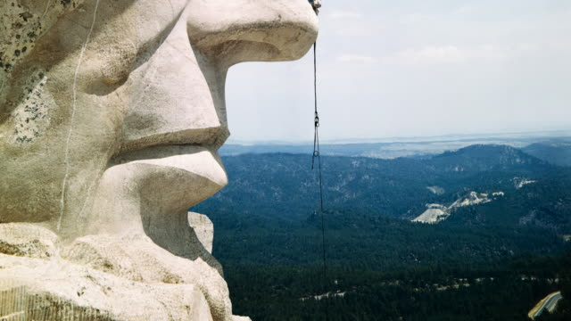 A repairman at Mount Rushmore rappels down the nose of the Abraham Lincoln sculpture.