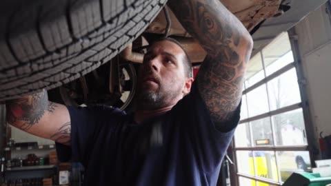 repairman - bilmekaniker, kaukasisk vit man med tatueringar på händerna, som arbetar i en bilverkstad - fastställande fjädring av bilen förhöjd på hissen. - hängbro bildbanksvideor och videomaterial från bakom kulisserna