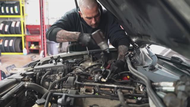 vidéos et rushes de réparateur - mécanicien d'automobile, homme blanc caucasien avec des tatouages sur des mains, travaillant sous le capot d'un atelier de réparation de voiture. - capot de voiture