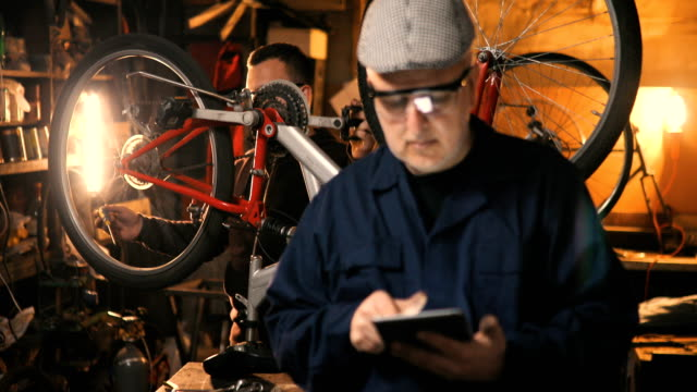 repairman repairing bicycle in workshop using tablet - workshop stock videos & royalty-free footage