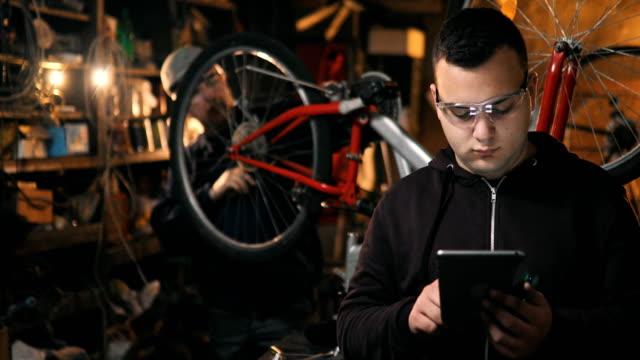 vídeos de stock, filmes e b-roll de técnico de reparação de bicicletas na oficina usando tablet - vendendo
