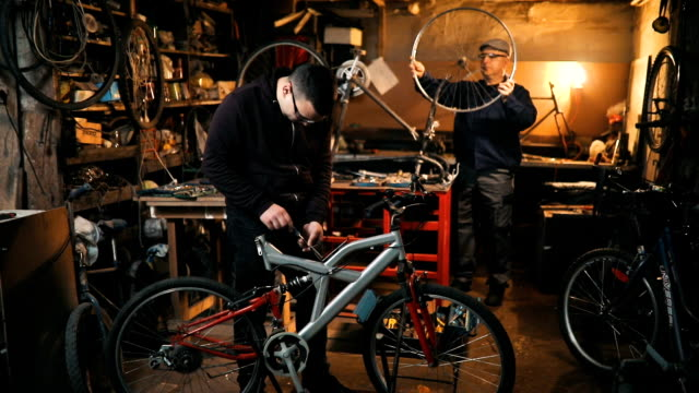 vídeos de stock, filmes e b-roll de bicicleta de reparação reparador na oficina - peça de máquina