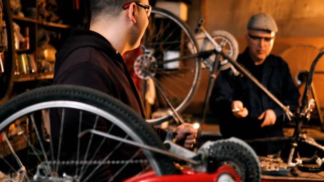 vídeos de stock, filmes e b-roll de bicicleta de reparação reparador na oficina - consertando