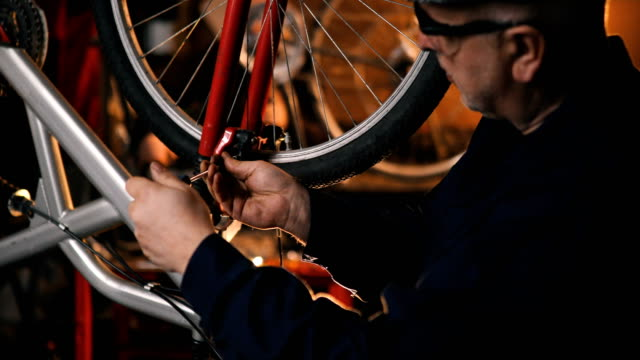 repairman repairing bicycle in workshop - riparare video stock e b–roll