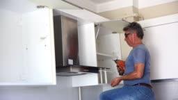 repairman repairs kitchen cabinets