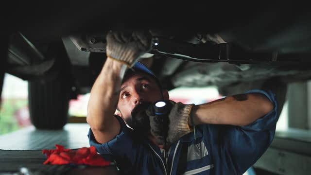 stockvideo's en b-roll-footage met reparateur die aan een voertuig in een autodienst werkt. - auto industrie