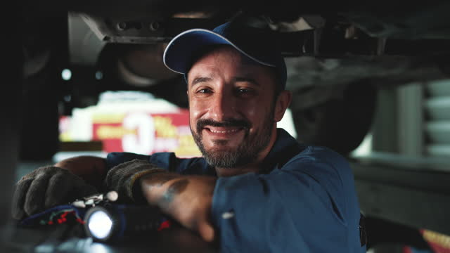 repairman working on a vehicle in a car service. - machine part stock videos & royalty-free footage