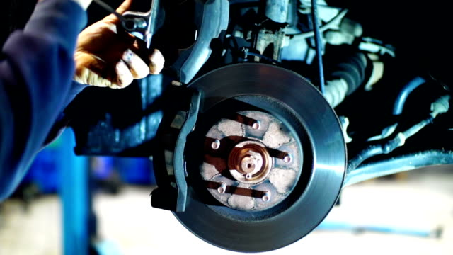 replacing brake pads on a car at a workshop. - repair garage stock videos & royalty-free footage