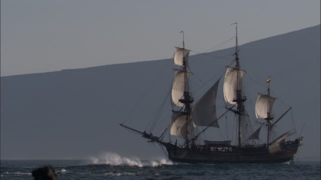 replica of hms endeavour sails past coast. - nave a vela video stock e b–roll