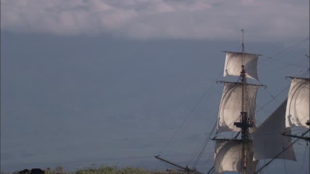 Replica of HMS Endeavour sails past coast.