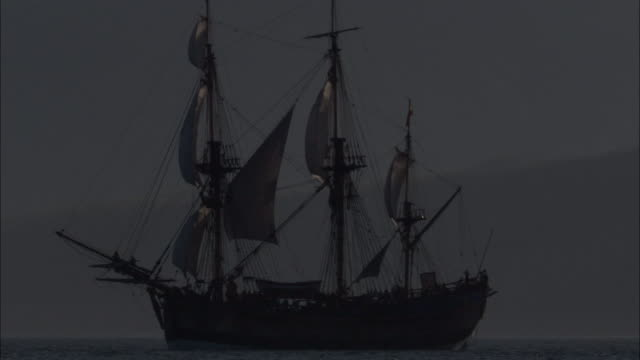 Replica of HMS Endeavour under full sail at dusk.