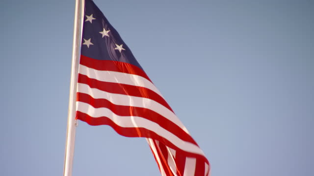 CU Replica of Star Spangled Banner flapping in wind at Fort McHenry against blue sky / Baltimore, Maryland, United States