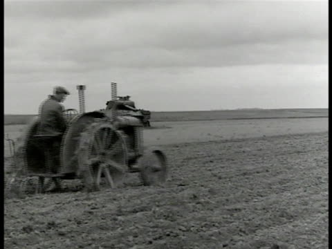 stockvideo's en b-roll-footage met report 'agriculture' ws french farmer driving tractor plowing destroyed german tank bg ws farmers tractor harrowing ws cows on farm ws cows walking... - 1946