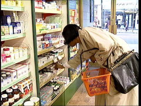 report dismisses vitamin illness benefits woman picking up packets of vitamins in health food shop ltn - health food shop stock videos and b-roll footage
