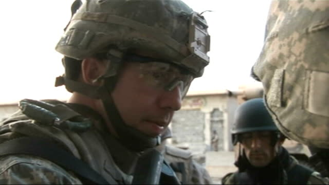 report from mosul on how american army are facing sunni and teenage insurgents track behind us soldier as along to checkpoint american soldier... - 言語翻訳点の映像素材/bロール