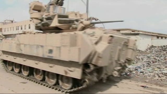 report from mosul on how american army are facing sunni and teenage insurgents american bradley tank along street past wreckage of another reporter... - caterpillar track stock videos and b-roll footage