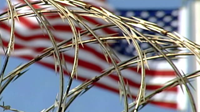 report on cia 'brutal' interrogation methods; r12090610 / 12.9.2006 cuba: guantanamo bay: ext barbed wire with american flag flying in background... - insignier bildbanksvideor och videomaterial från bakom kulisserna