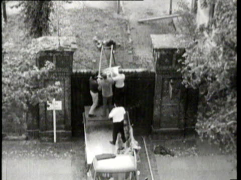 vidéos et rushes de report on east berlin escape through cemetery / young soldiers at upper floor window with guns / cemetery grave stones next to barbed wire / german... - évasion