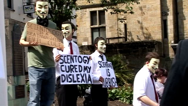 report on 'hacktivist' group anonymous; lib sussex: protesters holding up anti-scientology placards masked protester handing out leaflets - アノニマス点の映像素材/bロール