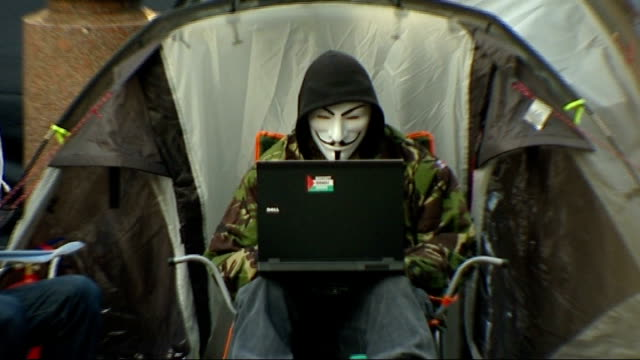 report on 'hacktivist' group anonymous; t29111106 ext protester wearing guy fawkes mask using laptop computer as sits outside tent pull out - アノニマス点の映像素材/bロール
