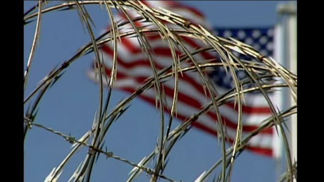 report on outgoing us vice president dick cheney; date unknown: cuba: guantanamo bay: ext barbed wire on top of wall at us prison camp, with us flag... - dick cheney stock videos & royalty-free footage
