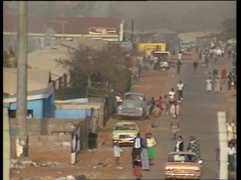 report on soweto; south africa: soweto: barbed wire fence pull people in street in gts township and dwellings kids jumping on trampolines - ソウェト点の映像素材/bロール