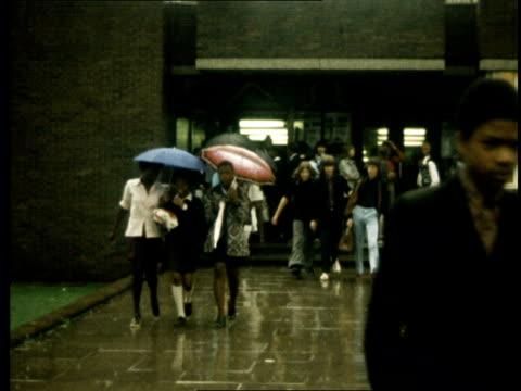 report on truancy amongst school children england london willesden ms boys leave school in rain towards followed by 3 girls ms bots girls towards ks... - 1973 stock-videos und b-roll-filmmaterial