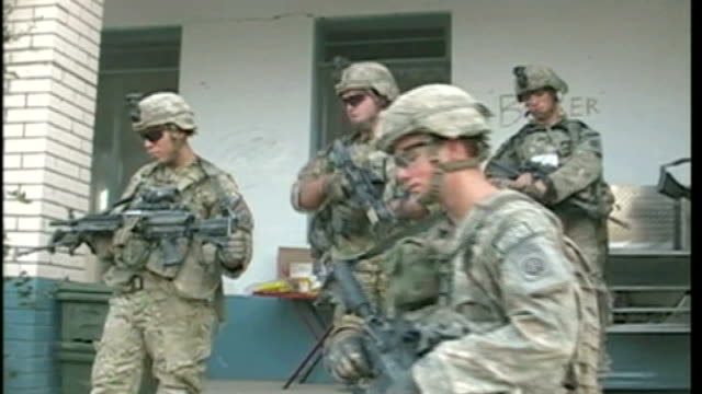 report on us troops; us soldiers leaving schoolhouse to go on patrol and soldiers wallking along on track soldier reloading rifle - schoolhouse stock videos & royalty-free footage